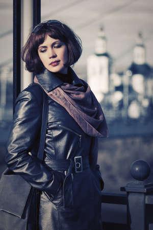 Sad beautiful fashion woman outdoor Stylish female model wearing black leather coat with bob hairstyle