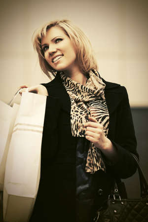 Happy young fashion woman with shopping bags at the mall Stylish female model wearing classic black coat