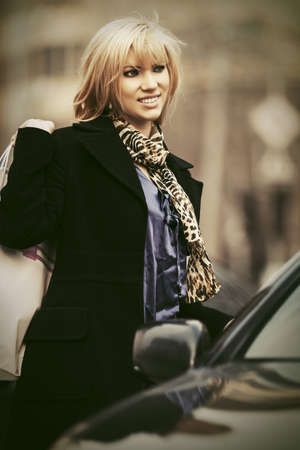 Happy young fashion woman with shopping bags next to her car Stylish female model in classic black coat Фото со стока