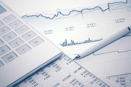 Financial accounting stock market graphs and charts analysis pen and calculator on balance sheets