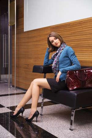 Mujer de negocios de moda joven sentada en el sofá en el interior de la oficina Elegante modelo femenino vistiendo rebeca azul y falda lápiz negra