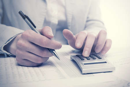Financial accounting business woman using calculator in office Archivio Fotografico