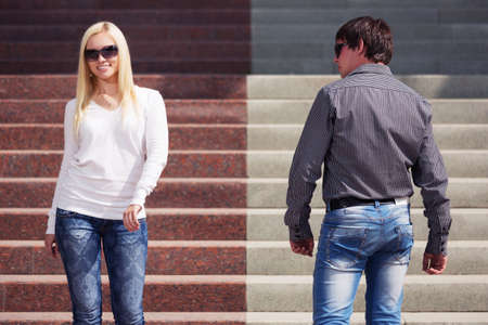 Young fashion couple flirting on city street Stylish trendy man and woman in sunglasses and blue jeans