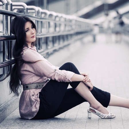 Sad young fashion woman sitting on the street sidewalk Stylish female model wearing black pants and pink shirt