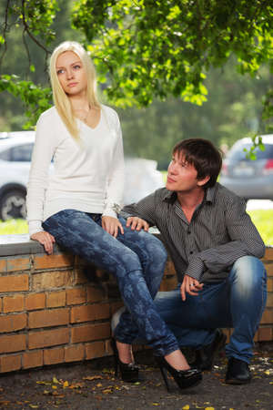 Young couple in conflict on city street Stylish trendy man and woman in long sleeve shirts and blue jeans