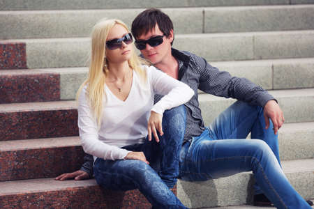 Happy young fashion couple on the steps Stylish trendy man and woman in  sunglasses and blue jeans