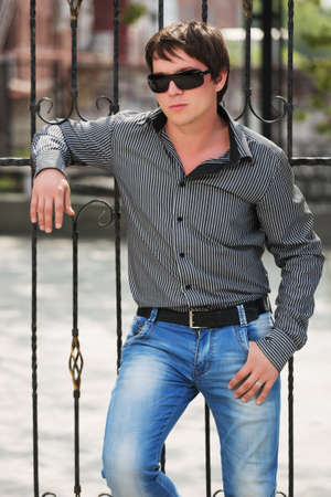 Young handsome man in sunglasses and striped shirt leaning at cast iron fence on city street