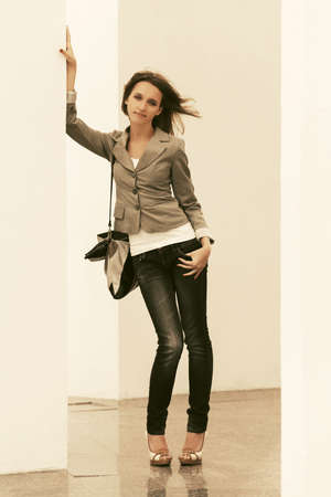 Happy young fashion woman with handbag leaning on the wall  Stylish female model gray blazer and dark blue jeans