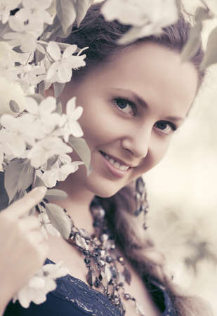 Happy beautiful woman walking in a spring blooming garden  Stylish fashion model with braid hair style