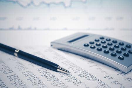Financial accounting stock market graphs and charts Pen and calculator on balance sheets