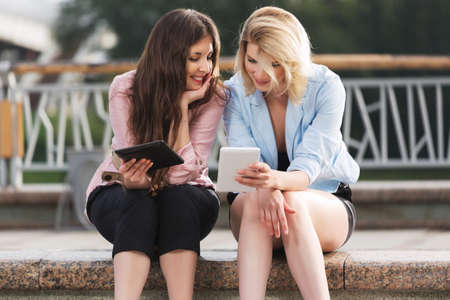 Two young fashion women using digital tablet computer on city street Stock Photo