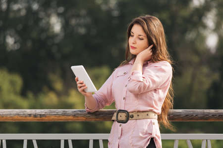 Young fashion woman using digital tablet computer outdoor Stylish female model with long brown hairs in pale pink shirt Stock Photo