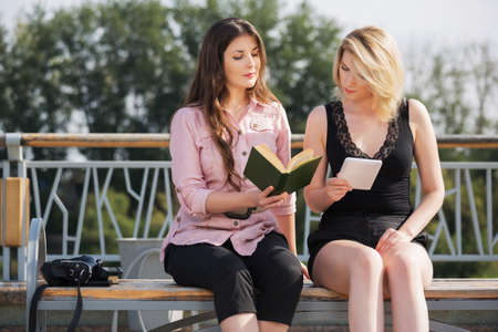 Two young fashion women reading a book on city street Stock Photo