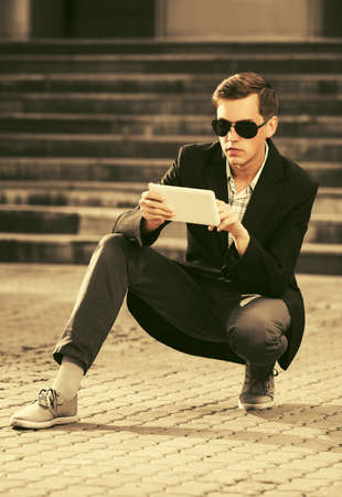 Young handsome business man using tablet computer on city street Stylish trendy male model wearing sunglasses and black suit jacket Stock Photo