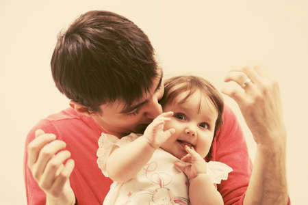 Happy young father and six months old baby girl at home 免版税图像