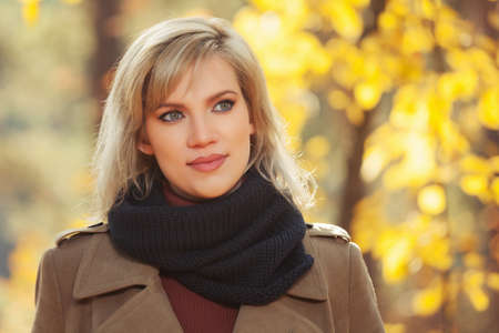 Happy young blonde fashion woman with handbag walking in autumn park Stylish female model wearing classic beige coat and black scarf Stockfoto