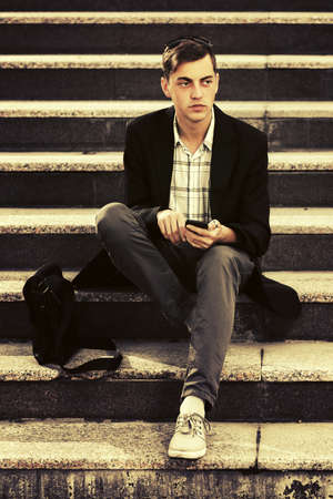 Young business man with cell phone sitting on steps Stylish male model in black blazer and gray pants Stok Fotoğraf