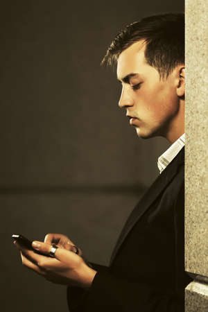Young handsome business man using cell phone on city street Stylish fashion male model in black blazer  Stok Fotoğraf