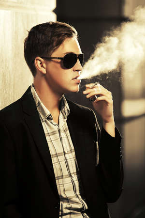 Young man in sunglasses smoking a cigarette on city street  Stylish fashion male model wearing black suit jacket Stok Fotoğraf - 133080394