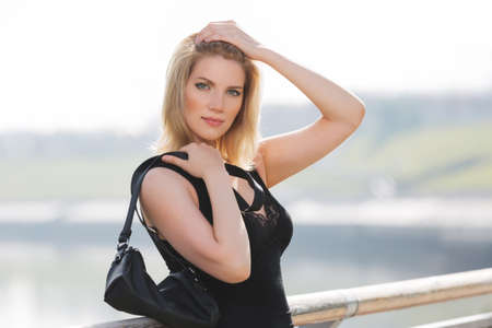 Happy young blonde fashion woman with handbag Stylish female model in black tank top Imagens