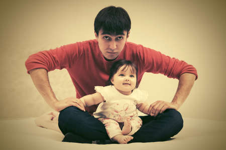 Happy young father and baby girl sitting on blanket at home