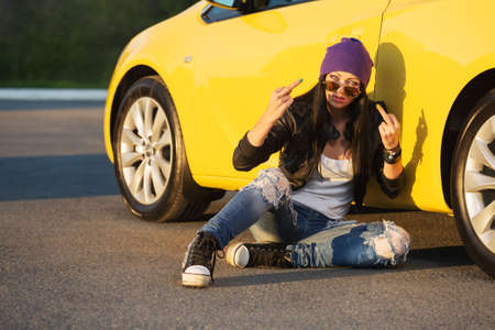 Angry young fashion hipster woman in sunglasses sitting on sidewalk leaning on car  Stylish female model in black leather jacket purple beanie and ripped jeans