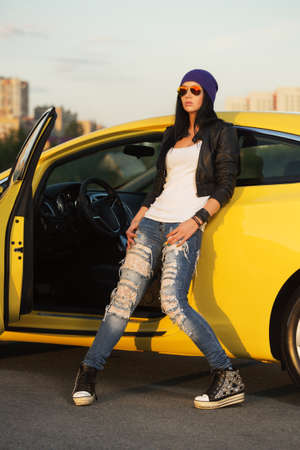Young fashion hipster woman in sunglasses leaning on her car  Stylish female model in black leather jacket purple beanie and ripped jeans