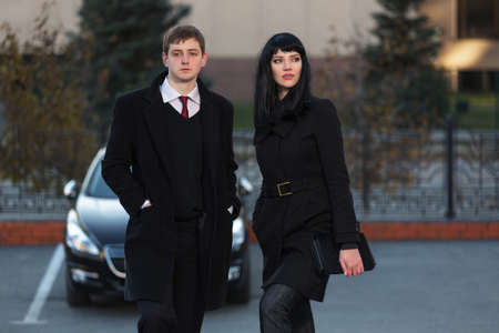 Young fashion business couple on city street Stylish man and woman in classic black coats Banque d'images