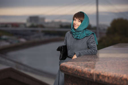 Young fashion woman with handbag leaning on parapet Stylish female model in gray classic coat and head scarf Archivio Fotografico