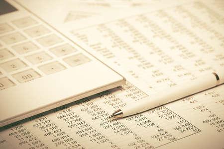Financial accounting Pen and calculator on balance sheets Stock Photo