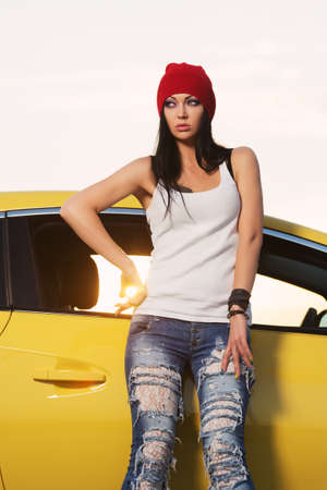 Young fashion hipster woman leaning on her car Stylish female model in white tank top red beanie and ripped jeans