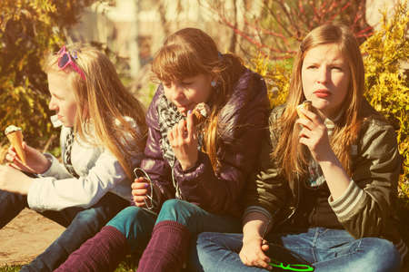 Group of happy teenage girls eating an ice cream outdoor