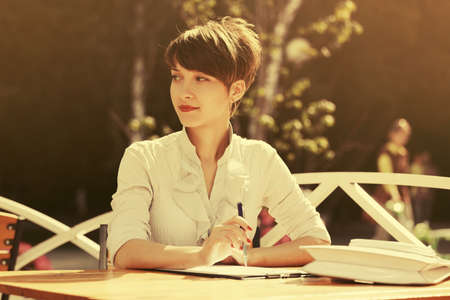 Happy young business woman working at sidewalk cafe. Stylish fashion female model in white shirt outdoor