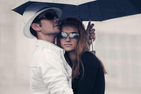 Junges Modepaar verliebt in Regenschirm Stilvoller Mann und Frau, die sich auf der Stadtstraße umarmen