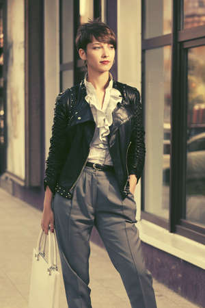 Happy young fashion woman in leather jacket with handbag walking in city street Stock Photo