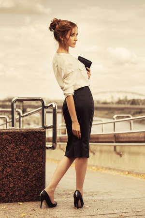 Young business woman with handbag walking on city street Stylish fashion model with bun updo hair wearing white shirt and black pencil skirt