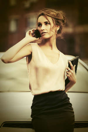 Young business woman with handbag calling on cell phone on city street Stylish fashion model in white sleeveless shirt and black skirt