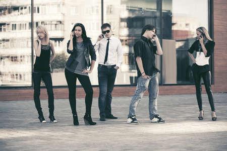 Junge Modeleute, die Handys auf der Stadtstraße benutzen Stilvolle, trendige Männer und Frauen