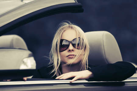 Young fashion blonde woman in black blazer and sunglasses driving convertible car