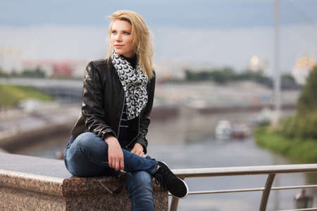 Happy young fashion blonde woman sitting on parapet Stylish trendy model in black leather jacket and silk scarf
