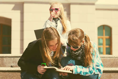 Group of happy teenage school girls reading a book in campus