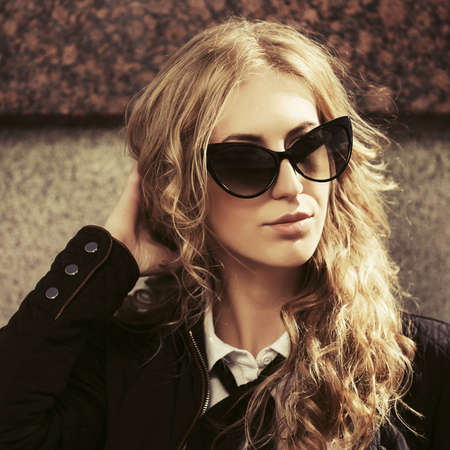 Young fashion blonde business woman Stylish female model in black jacket and sunglasses Foto de archivo