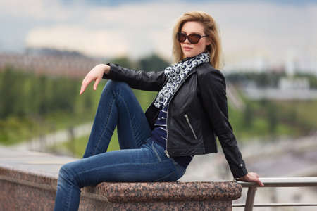 Happy young fashion blonde woman sitting on parapet Stylish trendy model in black leather jacket silk scarf and sunglasses