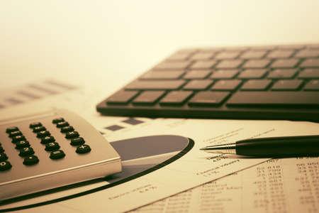 Financial accounting stock market graphs and charts analysis Calculator and computer keyboard on balance sheets