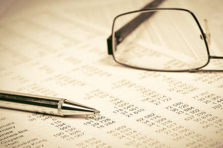 Financial accounting Pen and eyeglasses on balance sheets Archivio Fotografico
