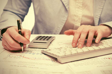 Financial accounting Business woman using calculator and computer keyboard in office