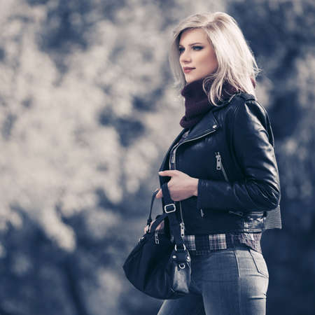 Young fashion blonde woman with handbag walking on city street Stylish female model in black leather jacket and snood scarf Standard-Bild