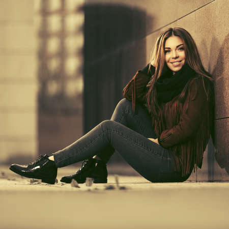 Happy young fashion woman sitting on city street sidewalk Stylish female model in brown leather fringe suede jacket and dark blue jeans