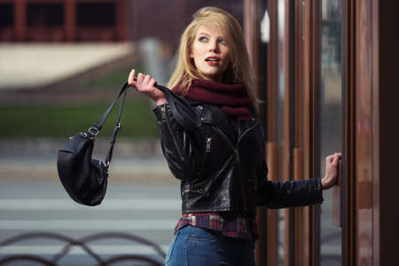 Young fashion blonde woman with handbag at the mall doorway Stylish female model in black leather jacket and snood scarf
