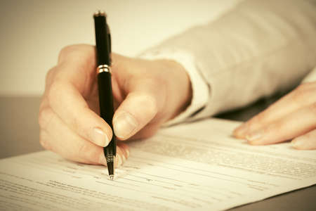 Close-up of business woman signing contract